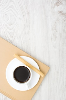 Coffee and wafer on book and white wooden table