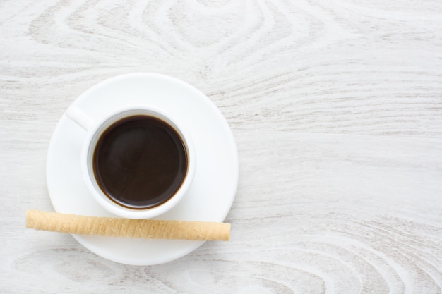 Coffee and wafer on white wooden table copy space
