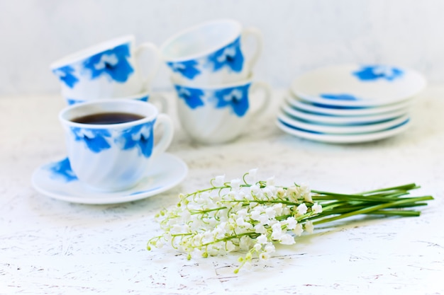 Coffee on white background and flowers. lilies of the valley. spring. morning. march 8. women's day
