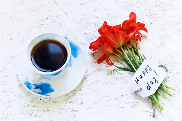 Coffee on white background and flowers. tulip. spring. morning. march 8. women's day