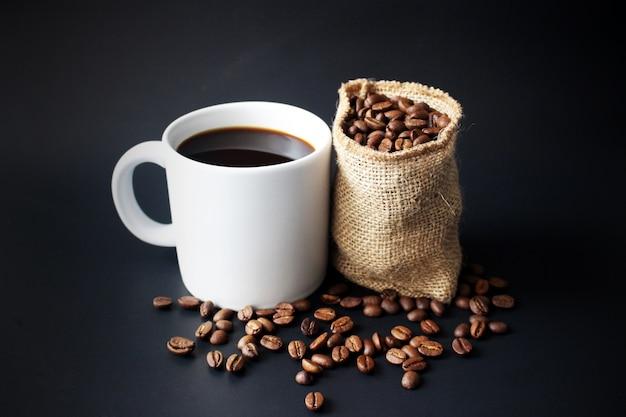 Кофейная чашка белого цвета и кофейные зерна в мешочке на черном фоне