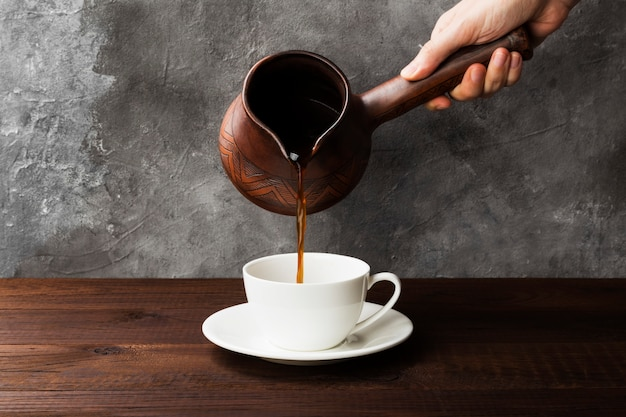 Coffee in white cup and clay cezve on wooden background