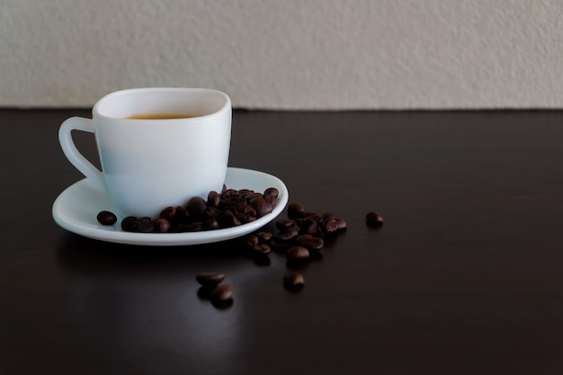 Coffee in a white cup and coffee beans on the table