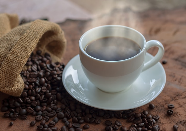 Coffee in a white cup and coffee beans on a wooden table