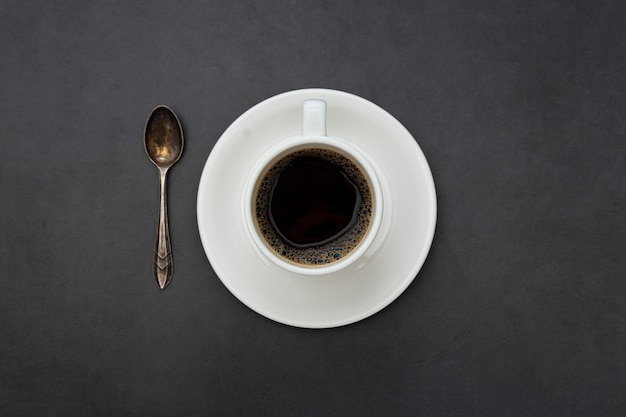 Coffee. white cup of coffee top view spoon and plate on dark background