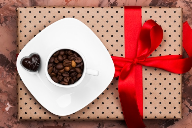 Coffee in white cup, gift with red tape and chocolates. top view. food background