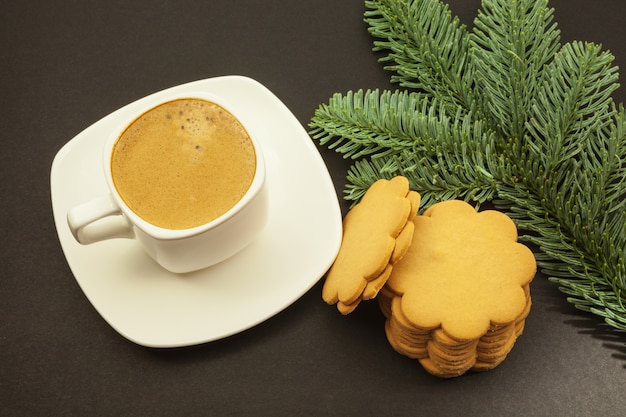 Coffee in a white cup and ginger cookies with a fir branch on a dark background