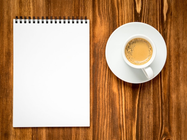 Coffee in white cup and open notepad with a clean white page on brown wooden table, top vi