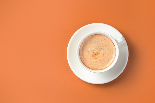Coffee in a white cup and saucer on a terracotta background. morning cappuccino. top view, copy space.