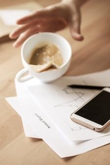 Caffè in tazza bianca che si rovescia sulla tavola di mattina alla tavola dell'ufficio