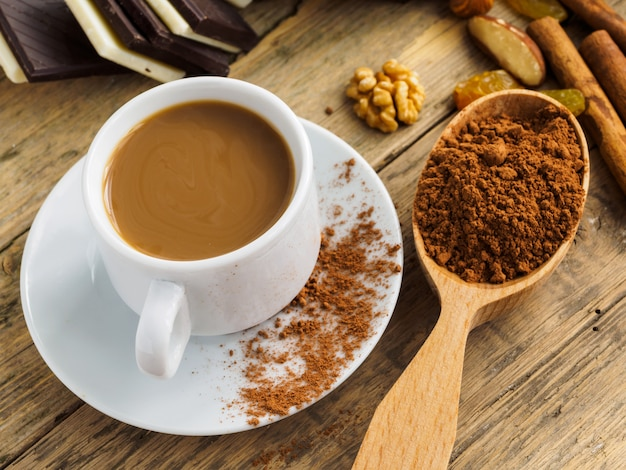Coffee in a white cup, sweets and scattered cinnamon on a wooden table