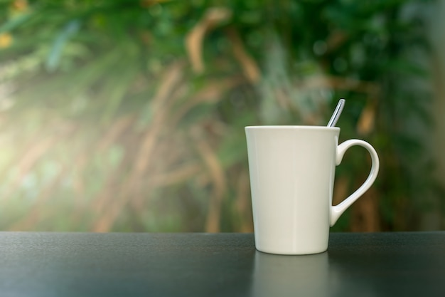 Coffee in a white cup on the table in the garden