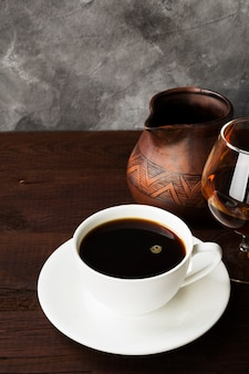 Coffee in white cup with cognac and clay cezve on wooden table