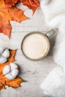 Coffee, white fluffy sweater on a white background and maple autumn leaves.