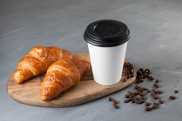 Coffee in white paper cup with lid and pair of fresh croissants on wooden cutting board.