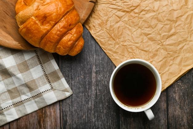 Кофе с круассаном. начало утра. чашка кофе. свежий французский круассан. кофейная чашка и свежие испеченные круассаны на деревянном. ,