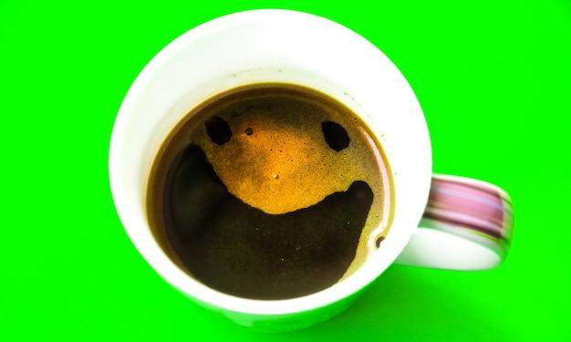緑の背景に分離された泡から笑顔でコーヒー。面白い写真。