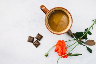 Coffee with beautiful rose and chocolate pieces on white background