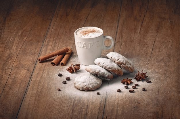 Coffee with biscuits and cinnamon on a brown board