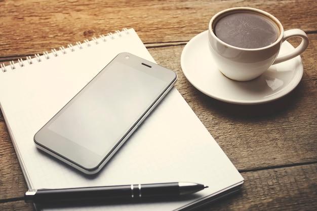 Кофе с пустым блокнотом и телефоном на деревянном столе