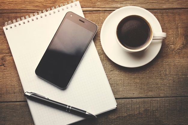 Coffee with blank notebook and phone on wooden table