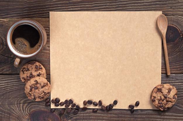 어두운 나무 배경에 텍스트를 위한 초콜릿 쿠키와 빈 갈색 종이가 있는 커피, 위쪽