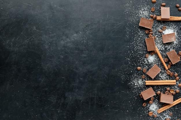 Кофе с шоколадным шугаром и корицей на черном фоне