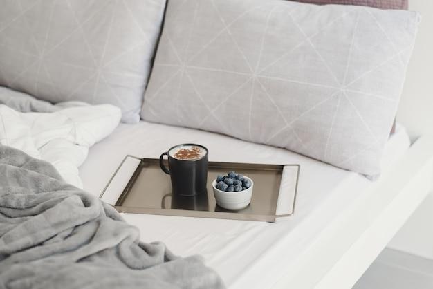Кофе с корицей и свежей черникой на металлическом подносе подается в постель