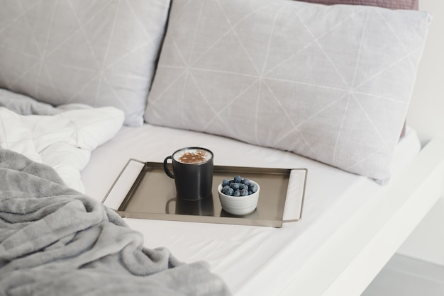 Coffee with cinnamon powder and fresh blueberry on metal tray served in bed