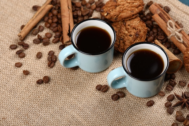 Coffee with coffee beans, cookies and cinnamon on a burlap.