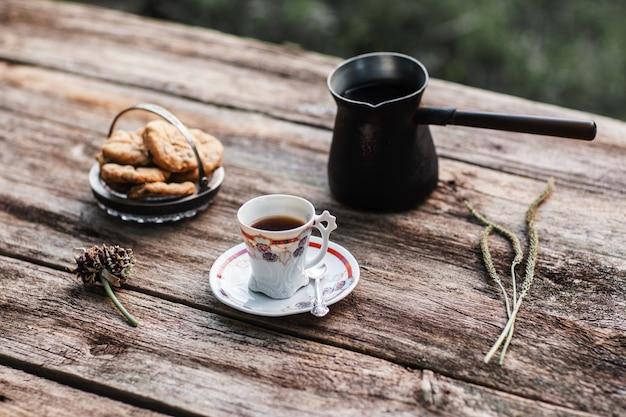 Кофе с печеньем на деревянном столе. традиционный кофе-брейк с выпечкой в деревенском стиле. осень, концепция согревающего напитка
