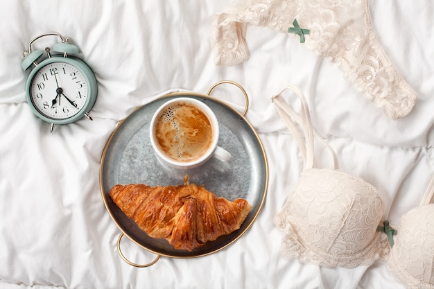 Coffee with croissant, alarm clock, girls underwear