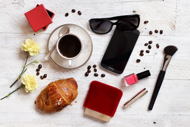 Coffee with croissant, cell phone, sunglasses and make up tools on a table
