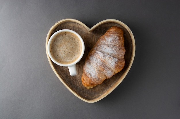 Coffee with croissant in wooden heart shaped box.