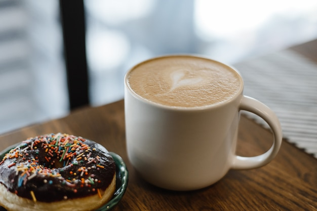 Coffee with a drawn heart and milk on a wooden table in a coffee shop. pink donut with scattering on the table next to the coffee