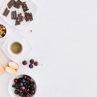 Coffee with dryfruit; chocolate pieces and fruits on white backdrop