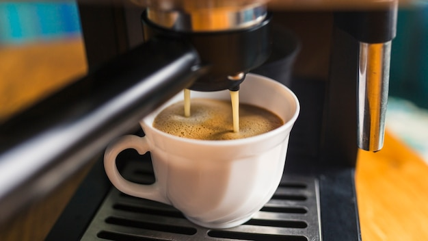 Coffee withfrothing pouring from espresso machine