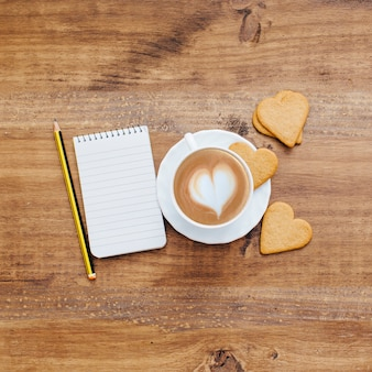 Coffee with heart biscuits and notebook