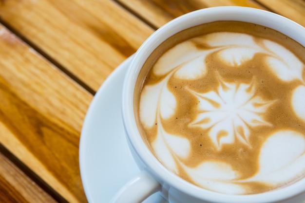 木製の背景にハート模様とコーヒー