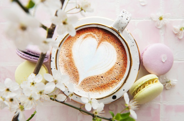 Coffee with a heart-shaped pattern and sweet macaroons desserts on a pink tile background