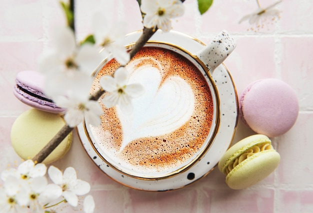 Coffee with a heart-shaped pattern and sweet macaroons desserts on a pink tile surface