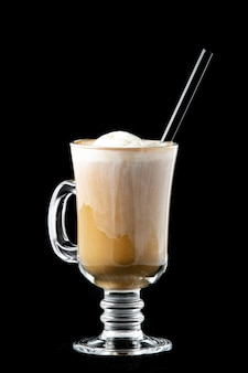 Coffee with ice cream in a glass in the glass there is a tube for drinking a drink of black color