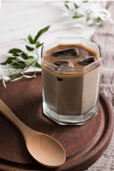 Coffee with ice cubes in glass and wooden spoon