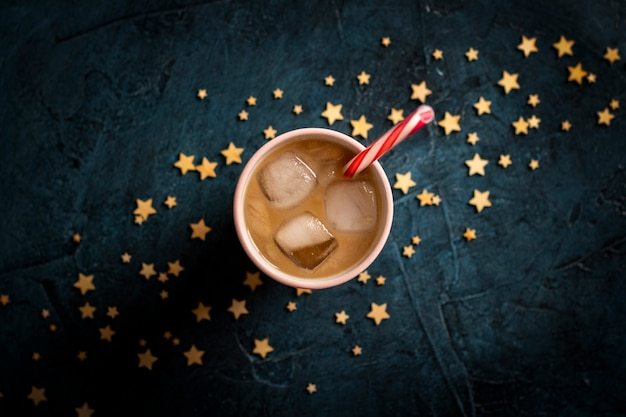 Coffee with ice and milk in a glass on a dark blue stone background with stars. concept cooling drink, thirst, summer, starry sky, nightlife, insomnia. flat lay, top view
