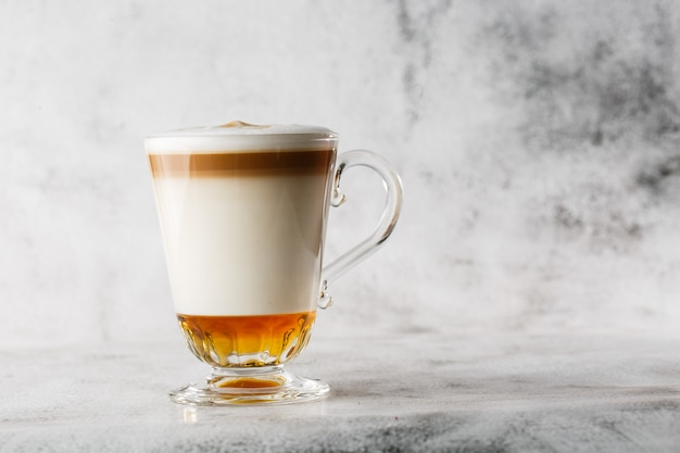 アイリッシュウイスキーと明るい大理石の背景に分離されたガラスのホイップクリームとコーヒー。俯瞰、コピースペース。カフェメニューの宣伝。コーヒーショップメニュー。横の写真。
