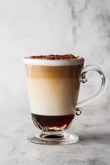 アイリッシュウイスキーと明るい大理石の背景に分離されたガラスのホイップクリームとコーヒー。俯瞰、コピースペース。カフェメニューの宣伝。コーヒーショップメニュー。縦の写真。