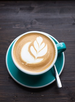 Кофе с латте-арт в керамической чашке на деревянном столе в кафе или кофейне вид сверху