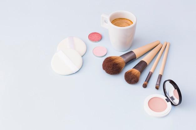 메이크업 브러시가 달린 커피; 아이 섀도우; 스폰지와 블러셔 무료 사진