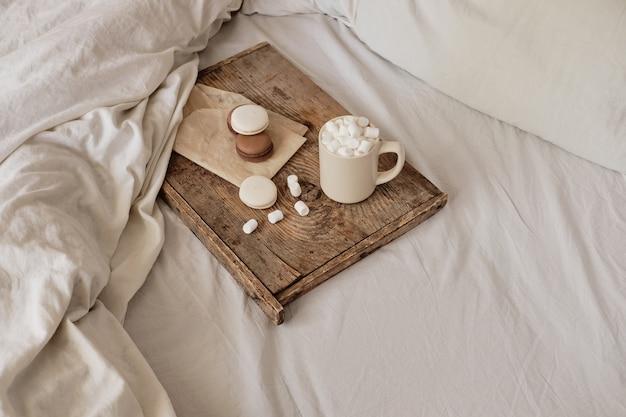 ベッドの中で、木製のトレイにマシュマロとマカロンを入れたコーヒー。審美的に美しいフレーム。ベッドの中でデザート。マシュマロ入りホットチョコレート。ベッドでの居心地の良い暖かい日