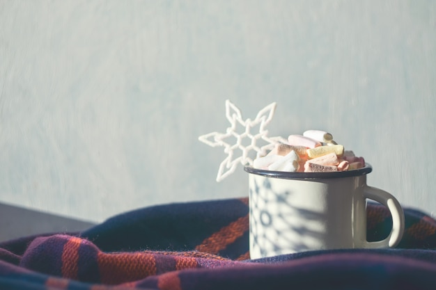 Coffee with marshmallows and decorative shiny snowflake